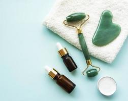 Massage du visage rouleau de jade sur fond vert pastel