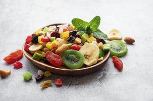 Bol avec divers fruits secs et noix sur un fond de béton gris photo