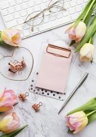 Lieu de travail indépendant ou blogueur avec clavier, bloc-notes et tulipes photo