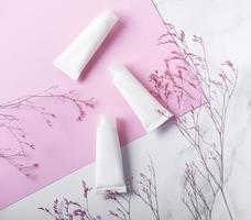 tubes blancs de crème sur fond de marbre et rose