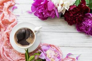 fleurs de pivoine rose et une tasse de café photo