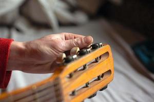 la main du musicien tord les mélodies de la guitare, accordant l'instrument photo