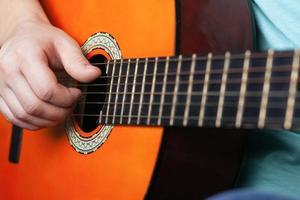 La main masculine joue des cordes de guitare acoustique photo