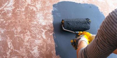concept de réparation à domicile, fille peint un mur photo