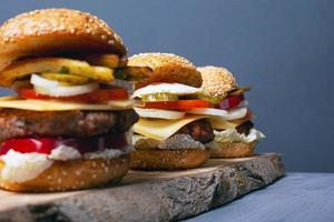 Trois hamburgers sur une forêt en bois se tiennent sur un fond gris photo
