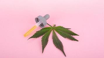 Feuille de cannabis et pipette avec extrait de concentré de thc psychoactif sur fond rose photo