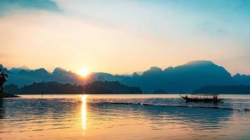 Image silhouette d'un bateau naviguant dans un barrage dans le sud de la Thaïlande photo