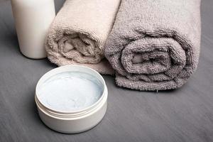 gommage corporel et serviettes pastel roulées pliées photo