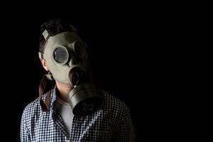 homme dans un masque à gaz sur fond noir, protection contre les virus photo