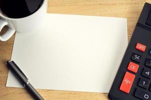 papier vierge sur table de bureau en bois avec tasse de café et calculatrice photo