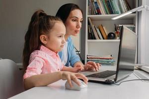 maman et fille installant un ordinateur portable pour une école virtuelle
