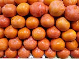 Fruits de kaki bio en tas au marché de producteurs locaux photo