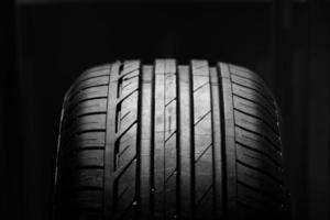 tourné en studio de pneu de voiture neuf isolé sur fond noir. fermer