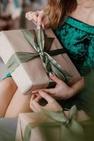 fille tenant un cadeau dans les mains, les femmes avec une boîte-cadeau dans les mains enveloppées dans du papier kraft décoratif avec un noeud de ruban vert attaché, vue de dessus, vacances concept, amour et soins photo