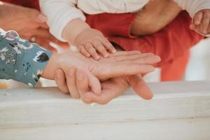 maman et papa tiennent la main de bébé. poignée pour enfants photo