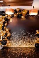 ballons dorés et noirs décorés de ballons noirs et jaunes. fête élégante avec des ballons. lieu de fête. photo