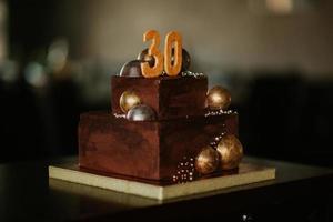 gâteau d'anniversaire au chocolat avec un numéro 30 décoré de boules de chocolat doré.