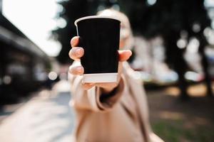 fille montrant une tasse de café en papier dans ses mains se bouchent