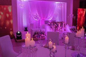 table de fête décorée de fleurs, de tissus et de chandeliers. décoration de mariage de luxe avec des lumières violettes. photo