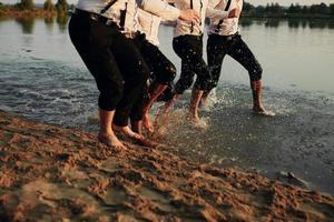 les pieds des hommes dans l'eau. les hommes en costumes courent sur l'eau. ils s'amusent, jouent et font des éclaboussures autour d'eux. l'été. Groupe de pieds heureux jeunes hommes éclabousser l'eau dans la mer et pulvériser sur la plage