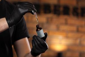 homme tenant l'huile essentielle pour barbe ou aromathérapie dans une bouteille en verre à portée de main et dégoulinant d'huile homme avec des gants noirs dans un salon de coiffure. copiez l'espace sur la bouteille.