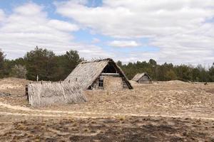 Ancien bâtiment rustique traditionnel avec un toit recouvert de paille au début du printemps, l'Ukraine. lieu touristique. photo