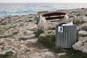 poubelle pleine ou poubelle avec bouteille en plastique, canettes de bière et déchets organiques montrant visiblement la pollution dans les zones côtières près de la mer. banc en bois avec seau avec des ordures sur le bord de mer rocheux. photo