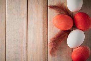 Oeufs de Pâques blancs et orange sur fond de bois clair photo