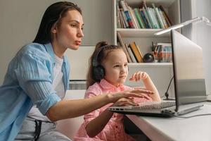 mère aidant sa fille frustrée avec l'école en ligne photo