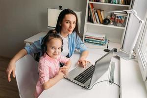 parent et enfant posant avec un ordinateur portable
