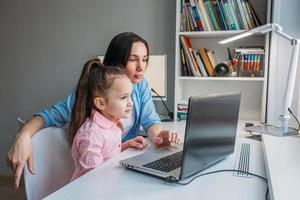 mère aidant sa fille à apprendre en ligne