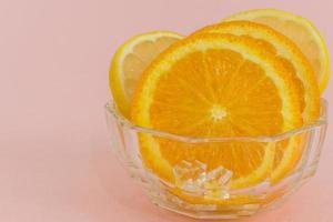 gros plan d'orange fraîche en tranches avec des glaçons sur fond rose. photo