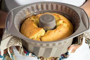 mains d'une personne tenant un moule en silicone avec un gâteau fait maison avec une serviette multicolore. mise au point sélective photo