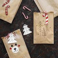 Sacs de cadeaux de Noël sur fond noir avec des cannes de bonbon