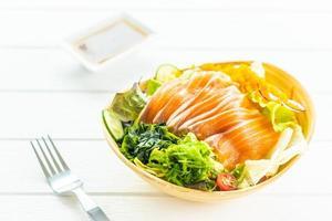 Sashimi de viande de poisson saumon frais cru avec salade d'algues et autres légumes photo