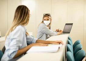 étudiante portant un masque médical de protection du visage pour la protection contre les virus à la salle de conférence photo