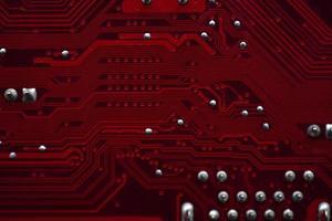Gros plan de puces de carte mère d'ordinateur rouge avec des contacts photo