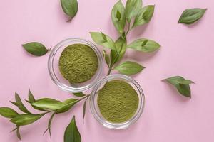 Poudre de matcha vert sur fond rose avec des feuilles photo