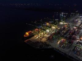 Jakarta, Indonésie 2021- Vue aérienne du chargement et du déchargement de porte-conteneurs dans un port en haute mer, importation logistique et transport de marchandises à l'exportation par porte-conteneurs en pleine mer la nuit photo