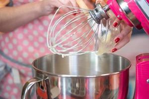 femme dans un tablier rose à l'aide d'un grand mélangeur photo