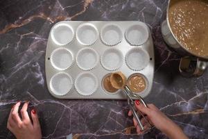 Femme avec plaque de cuisson pour faire des petits gâteaux sur un fond de marbre sombre