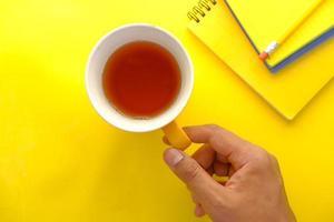 main tenant une tasse de thé vert sur fond jaune photo
