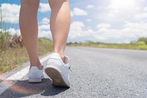 Femme qui marche sur une petite route de campagne avec fond de ciel bleu photo