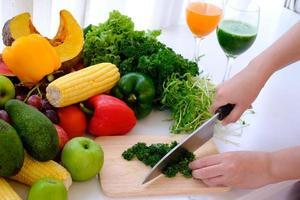Les mains à l'aide d'un couteau à hacher les légumes sur une planche à découper en bois photo