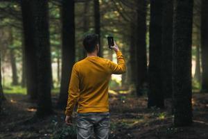 personne dans la forêt prenant des photos avec le téléphone