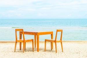 table et chaise en bois pour le dîner sur la plage photo