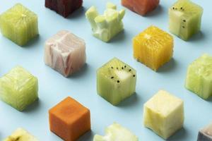 Composition de fruits et légumes en cubes sur fond bleu