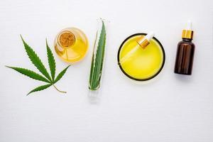 Bouteille en verre d'huile de cannabis et de feuilles de chanvre mis en place sur fond blanc