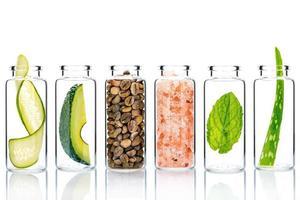 Soins de la peau alternatifs avec des ingrédients naturels dans des bouteilles en verre isolé sur fond blanc