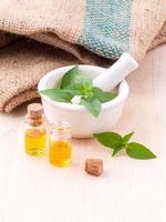Médecine alternative huile de basilic citron ingrédients naturels spa avec du mortier sur fond de bois